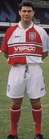 Mo Harkin models the new red and white quartered kit - on sale 1st June 2000